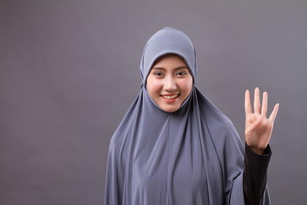 Kobieta wskazując numer 4 w górę, model azjatyckiej muzułmańskiej kobiety