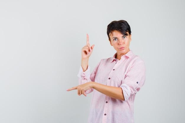 Kobieta wskazując palcami w górę iw dół w różowej koszuli i niepewny patrząc. przedni widok.