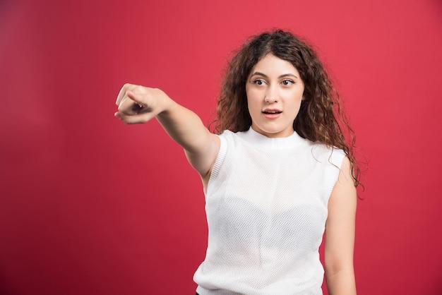 Kobieta wskazując palcem na aparat na czerwono.