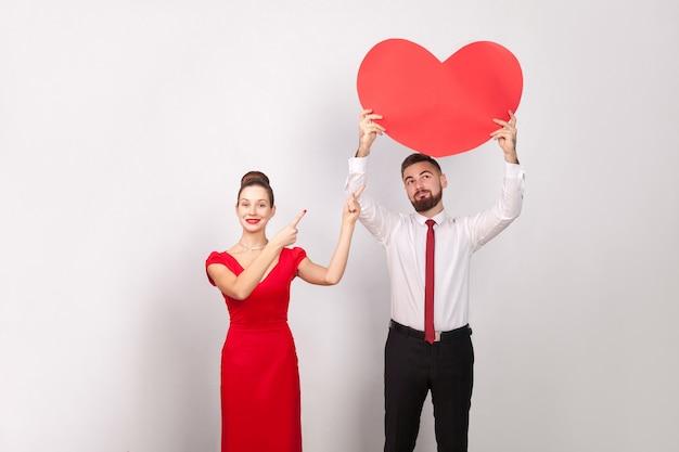 Kobieta, wskazując palcem na wielkie serce, mężczyzna patrząc na serce. wewnątrz, studio strzał, na białym tle na szarym tle
