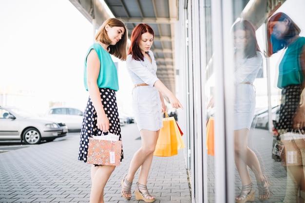 Kobieta wskazując swojego przyjaciela w oknie sklepu