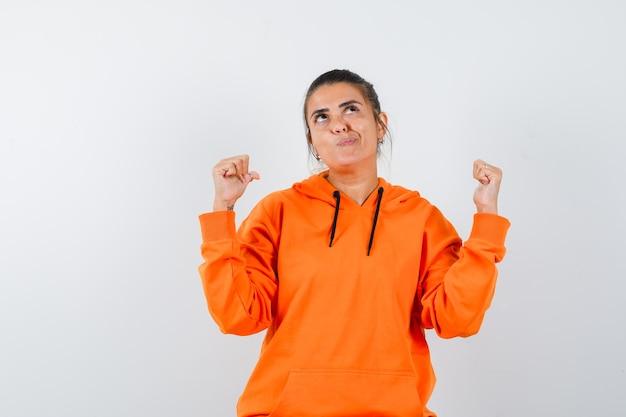 Kobieta wskazująca kciukami do tyłu w pomarańczowej bluzie z kapturem i patrząca z wahaniem