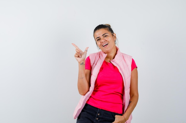 Kobieta wskazująca na lewy górny róg w koszulce, kamizelce i patrząca wesoło looking