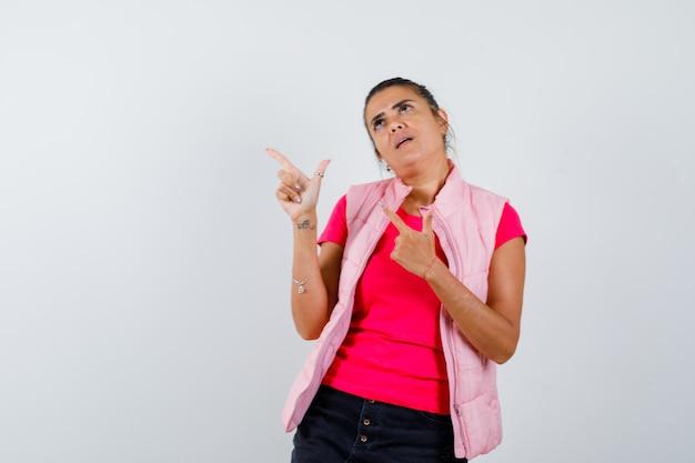 Kobieta wskazująca na lewy górny róg w koszulce, kamizelce i wyglądająca na zamyśloną