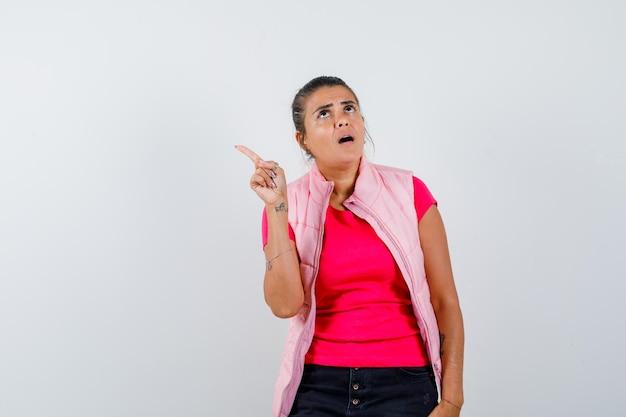Kobieta wskazująca na lewy górny róg w koszulce, kamizelce i wyglądająca na zdziwioną