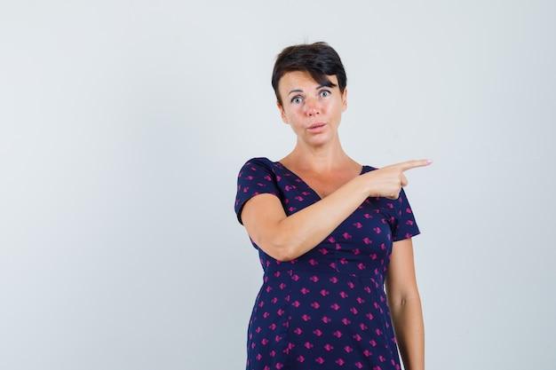 Kobieta wskazująca na prawą stronę w sukience i niezdecydowana.