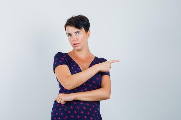 Kobieta wskazująca na prawą stronę w sukience i wyglądająca podejrzanie.