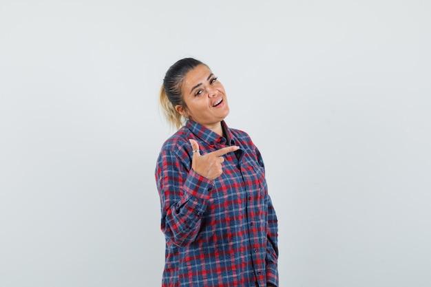 Kobieta wskazująca na prawą stronę w swobodnej koszuli i wyglądająca na pewną siebie, widok z przodu.