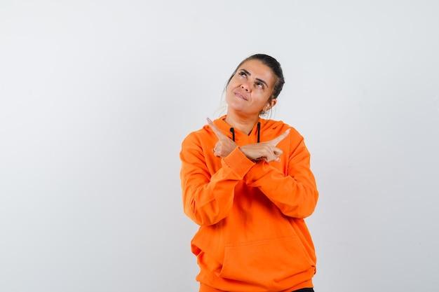 Kobieta wskazująca w pomarańczowej bluzie z kapturem i wyglądająca na marzycielską