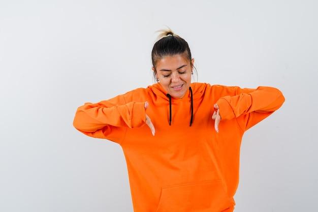 Kobieta wskazująca w pomarańczowej bluzie z kapturem i wyglądająca na skupioną