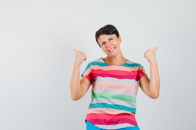 Kobieta wskazująca z kciuki w pasiastej koszulce i wyglądająca na zdezorientowaną. przedni widok.