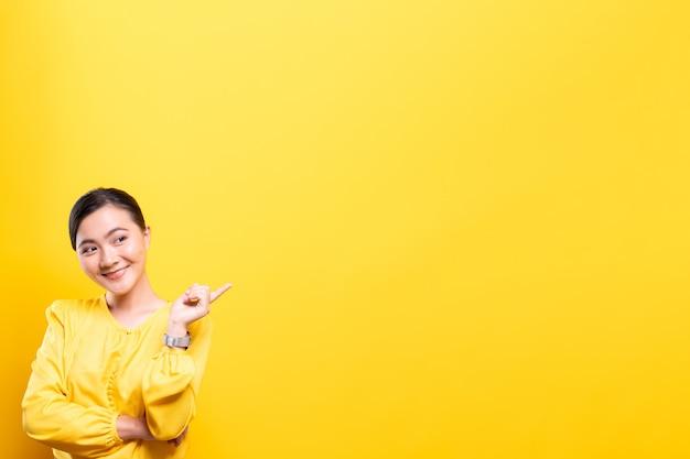 Kobieta wskazuje kopiować przestrzeń odizolowywającą nad kolor żółty ścianą
