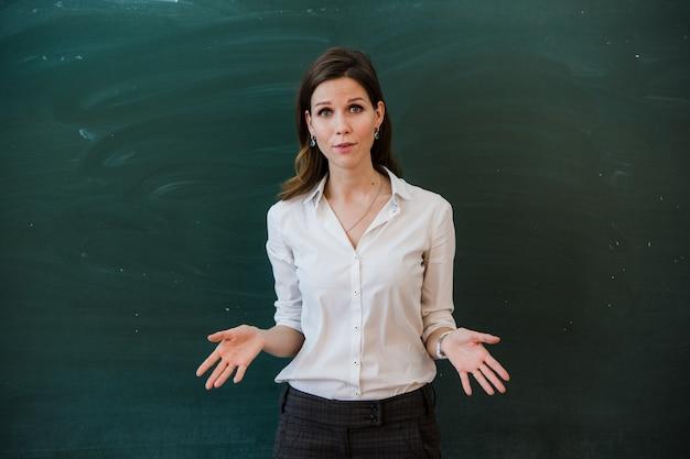 Kobieta wskazuje palec przy puste miejsce deską. nauczyciel wskazuje palcem na pustej planszy.