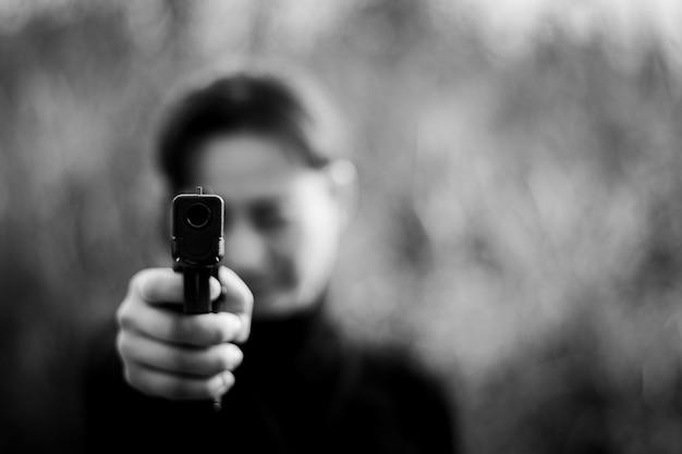 Kobieta wskazuje pistolet przy celem. - selektywna koncentracja na przednim pistolecie.