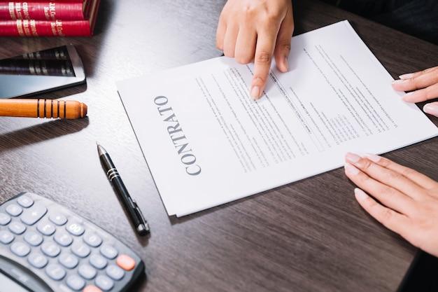 Kobieta wskazuje przy dokumentem blisko damy przy stołem z kalkulatorem, smartphone i piórem ,.