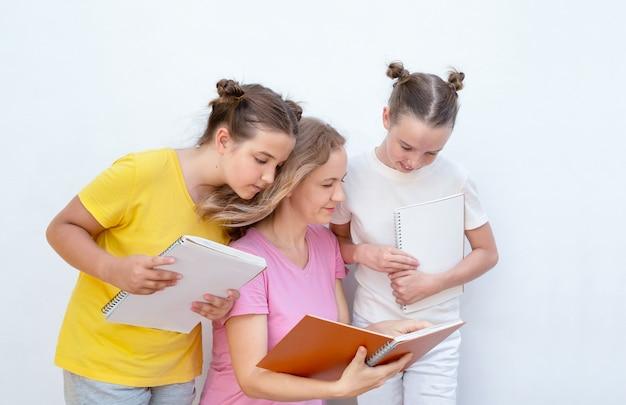 Kobieta wskazuje w zeszycie i wyjaśnia dzieciom.