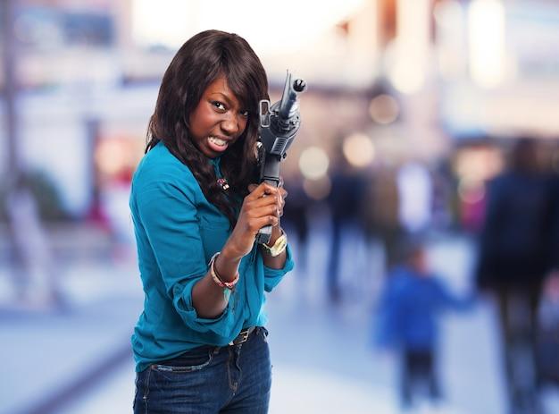 Kobieta wskazuje z karabinu maszynowego