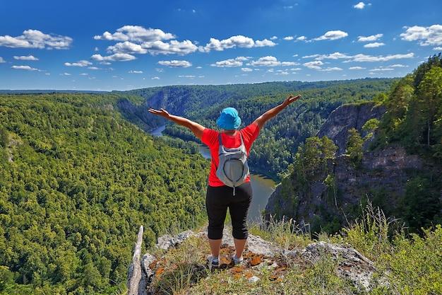 Kobieta wspięła się na szczyt góry, wędrując, raduje się ze swojego zwycięstwa, unosząc ręce.
