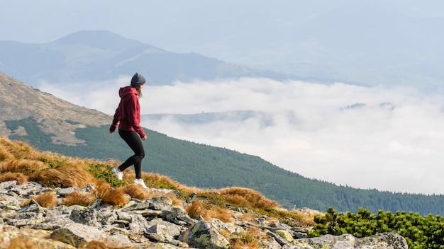 Kobieta Wspina Się Na Grzbiet Górski. Kobieta Przechodzi Przez Kamienną Dolinę W Górach Premium Zdjęcia