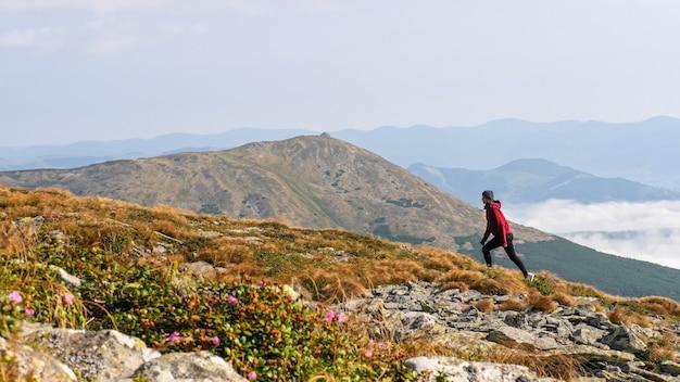 Kobieta wspina się na grzbiet górski. kobieta przechodzi przez kamienną dolinę w górach