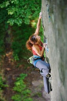 Kobieta wspinacz szuka następnego chwytu na trudnej skalnej ścianie na dużej wysokości z liną