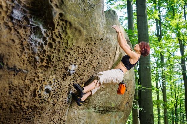 Kobieta wspinacz wspinaczka bez liny na skalistej ścianie