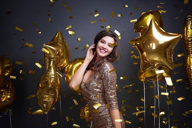 Kobieta wśród spadających balonów i konfetti