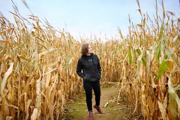 Kobieta wśród suszonych łodyg kukurydzy w labiryncie kukurydzy