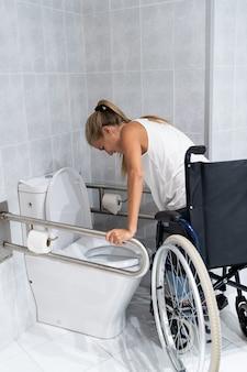Kobieta wstaje z rękami z wózka inwalidzkiego w toalecie