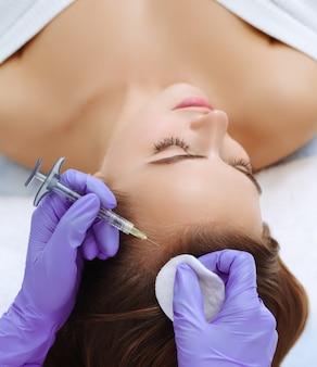 Kobieta wstrzykuje witaminy i minerały w skórę głowy