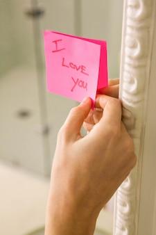 Kobieta wtykając kocham cię słowo karteczkę na lustro