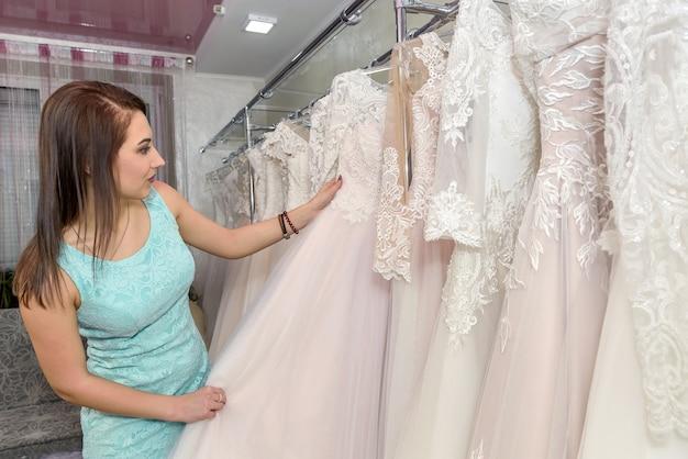 Kobieta wybiera białą suknię ślubną w sklepie panny młodej