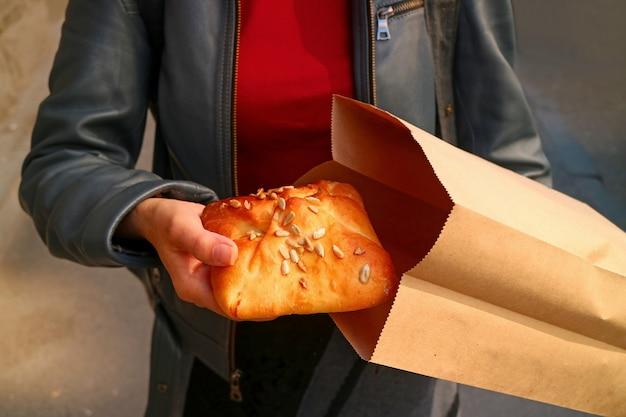 Kobieta wybiera ciasto francuskie z papierowej torby, koncepcja uratowania ziemi za pomocą nieplastycznych toreb