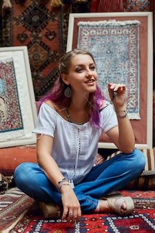 Kobieta wybiera dywan na rynku. orientalny bazar tekstyliów. fabryka do produkcji dywanów