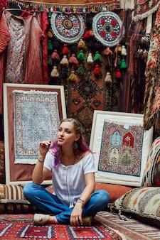 Kobieta wybiera dywan na rynku.