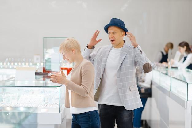 Kobieta wybiera klejnoty, mężczyzna w szoku ceną, sklep jubilerski. miłość para kupuje złotą dekorację w sklepie jubilerskim