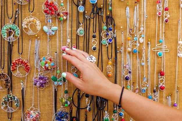 Kobieta wybiera kolorowe naszyjniki na targu turystycznym na malcie zbliżenie kobiet