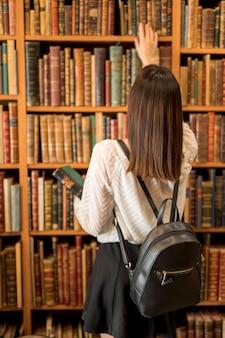 Kobieta wybiera książkę w bibliotece z plecakiem