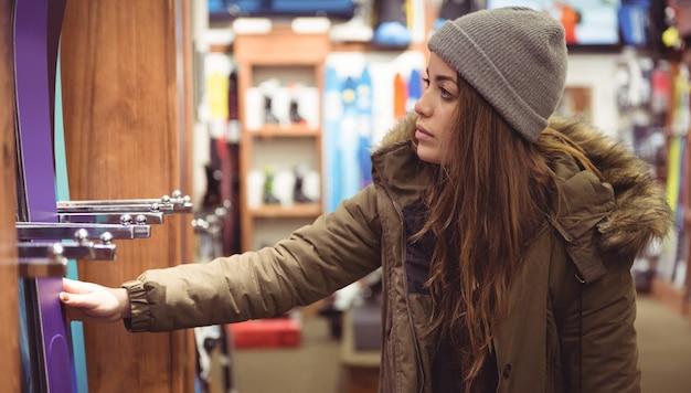 Kobieta wybiera narty w sklepie