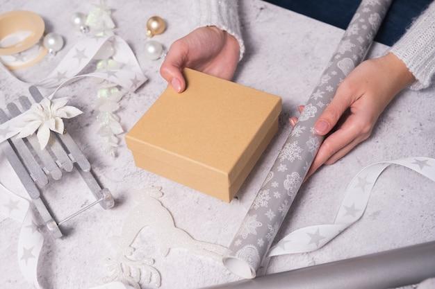 Kobieta wybiera papier do pakowania i ozdoby na prezent świąteczny.