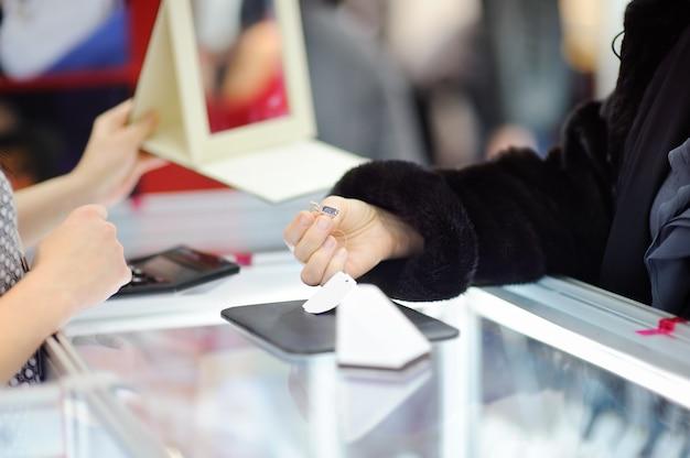 Kobieta wybiera perfect kolczyki przy jubilerem, zamyka w górę fotografii