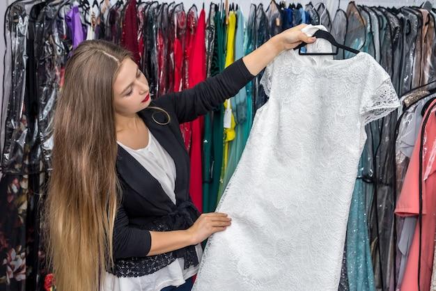 Kobieta wybiera piękną suknię wieczorową w sklepie sukienka