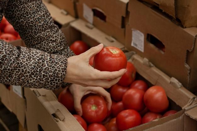 Kobieta wybiera pomidory w supermarkecie
