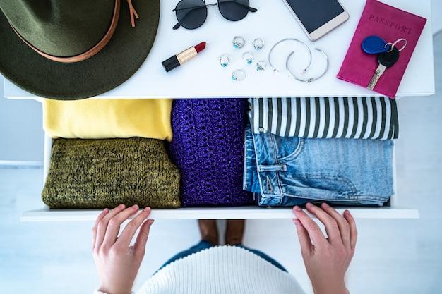 Kobieta wybiera strój z komody z szufladami ze stylowymi, modnymi, codziennymi ubraniami, artykułami domowymi i kobiecymi akcesoriami. widok z góry.