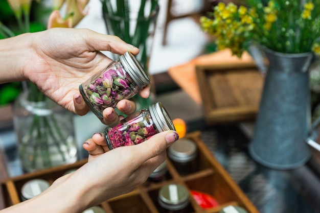 Kobieta wybiera suche kwiaty do robienia kwitnącej herbaty w szklanych butelkach z aluminiową pokrywką na rękach.
