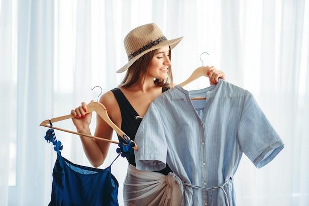 Kobieta wybiera sukienki, marzy o wakacjach