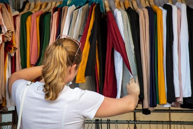 Kobieta wybiera ubrania przechodząc przez nadawcę w sklepie na targu. widok z tyłu