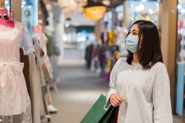Kobieta wybiera ubrania w centrum handlowym i jest ubranym medyczną maskę dla zapobiegania od koronawirusa