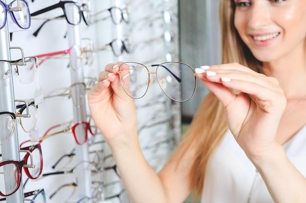 Kobieta, wybierając okulary w koncepcji optyki sklepu, wzroku i wizji.