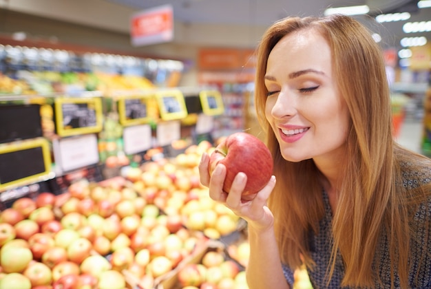 Kobieta wybierająca jabłka ze sklepu spożywczego